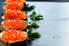 Red caviar on slate background. Royalty Free Stock Photography