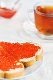Red caviar on a slice of bread and tea Stock Photography