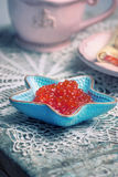 Red caviar in small starfish shaped bowl Stock Image