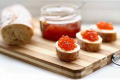 Red caviar in spoon. On a baguette Royalty Free Stock Photography
