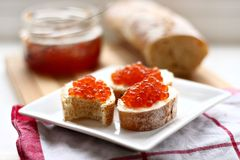 Red caviar in spoon. On a baguette Stock Photography
