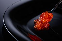 Red caviar in spoon. Red caviar in spoon on a black background Royalty Free Stock Image