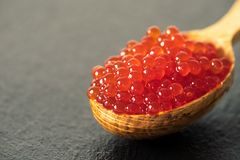 Red caviar in a spoon on a black slate background.  Stock Photo