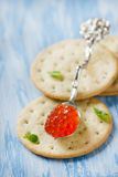 Red caviar in spoon on crackers Royalty Free Stock Images