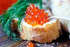 Red caviar. In spoon with dill twig and bread on wooden background. Selective focus Stock Photo