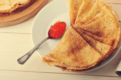 Red caviar in the spoon and pancakes in plate. On wooden background Royalty Free Stock Photos