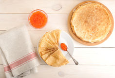 Red caviar in the spoon and pancakes in plate. On wooden background - top view Stock Photos