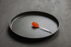 Red caviar in spoon. On a plate Stock Images