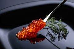 Red caviar in spoon. Red caviar in spoon on a black background Stock Images