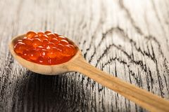 Red caviar in spoon. On wooden background Royalty Free Stock Image