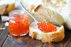 Red caviar. In spoon with white bread on wooden background. Selective focus Royalty Free Stock Image