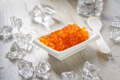 Red caviar with spoon on the wood background. White saucer with red caviar on the wood background, and little spoon Royalty Free Stock Photos