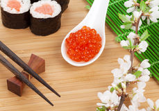 Red caviar, sushi set, sakura branch and chopsticks Royalty Free Stock Image