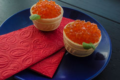 Red caviar in a tartlet. Old background. Top view. Close-up Royalty Free Stock Image