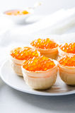Red caviar tartlets, appetizer canapes on bright background Royalty Free Stock Photography