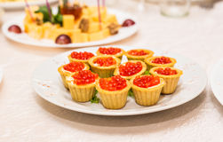 Red caviar in tartlets on white plate close-up Stock Photos