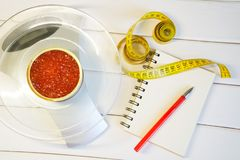 Red caviar in a tin can on the scales next to a notebook and a tape measure. Counting the amount of protein, calories and fat in stock images
