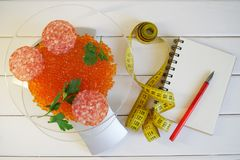 Red caviar, uncooked smoked sausage and parsley on the scales next to a notebook, fountain pen and tape measure. The amount of stock images