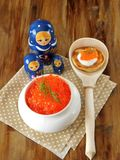 Red caviar in a white ceramic bowl and Russian dolls stock image