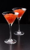 Red caviar in wineglasses on black background Stock Images