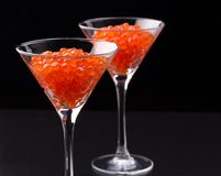 Red caviar in wineglasses on black background Stock Photography
