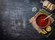 Red caviar in a wooden bowl. On old black background. Top view Royalty Free Stock Photography