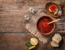 Red caviar in a wooden bowl. On old wooden table. Top view Stock Photo
