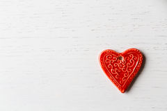 Red ceramic heart shaped decor. On a white wooden background Royalty Free Stock Images