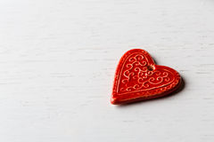 Red ceramic heart shaped decor. On a white wooden background Stock Photography