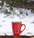 Red ceramic mug in a white polka dots with coffee. On a wooden surface, behind a blurred background with snow royalty free stock photography