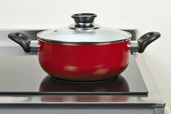Red ceramic pan with cover on Electric hob Royalty Free Stock Photos