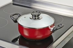 Red ceramic pan with cover on Electric hob Stock Photography