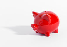 Red ceramic piggy bank or money box on white. With a shadow and copyspace in a conceptual financial image of savings and investment Royalty Free Stock Photo