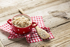 The red ceramic saucepan with white polka dots complete crumbly barley porridge. On a simple wooden background with a red cloth in a white cage with a wooden royalty free stock images