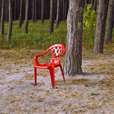 The red chair. Plastic a red chair stands on a wood edge Royalty Free Stock Photography