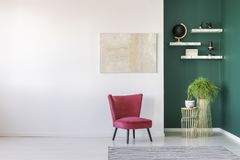 Modern living room interior. Red chair against white wall with painting in modern living room interior with shelves on green wall Stock Images