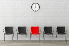 Red Chair with Another Black against wall with Modern Clock Stock Photography