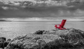 Red chair black and white nature background. A red Adirondack chair contrasts with a stormy black and white ocean background Stock Photo