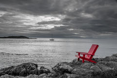 Red chair black and white nature background. A red Adirondack chair contrasts with a stormy black and white ocean background as a sailboat glides past