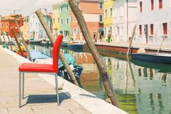 Red chair by the canal and Colorful houses in Burano island near Stock Images