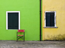 Red chair on colored background. In Burano, Venice Stock Photos