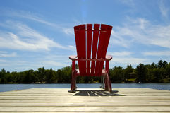 Red Chair On Deck Horizontal. A lone wooden chair sitting on the dock with a lake and cottages across in the background - horizontal orientation.  Perfect for Royalty Free Stock Photography