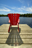 Red Chair On Deck Vertical. A lone wooden chair sitting on the dock with a lake and cottages across in the background - vertical orientation.  Perfect for Royalty Free Stock Images
