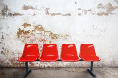 Red chair in empty room against a vintage buildings exterior bri. Ck wall background, commercial and marketing concept, copy space for text or media content Stock Photo
