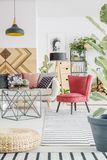Red chair in living room. Red chair on striped carpet next to table and beige settee in living room interior with lamp Stock Photography