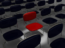 Red chair in many black chairs Stock Image