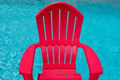 Red chair next to swimming pool Royalty Free Stock Images