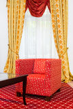 Red chair in the room with vintage red carpet and classic yellow drapes Stock Images
