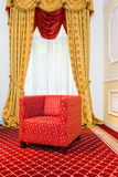 Red chair in the room with vintage red carpet and classic yellow drapes. Empty red chair in the room with vintage red carpet and classic yellow drapes royalty free stock photo