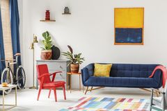 Red chair and royal blue lounge placed in bright sitting room in. Terior with colorful carpet, modern art painting, fresh plants and gold lamp next to grey stock images
